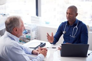 Senior Male Patient In Consultation With Doctor Sitting At Desk