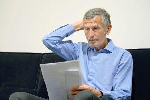 Worried man opens letter - Negative