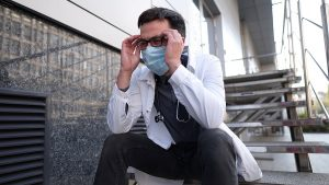 Worried And Tired Doctor Sitting On Stairs Outside Hospital
